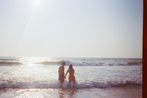 A couple hand-in-hand at Candolim beach